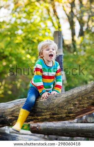 Little kid boy in colorful shirt with stripes and gumboots having fun with playing on playground on warm, autumn day, outdoors - stock photo