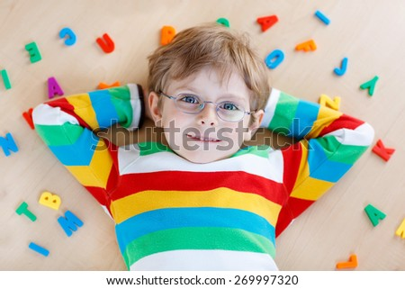 Little kid boy in eyeglasses playing with lots of colorful plastic letters, indoor. Child wearing colorful shirt and having fun with learning reading - stock photo