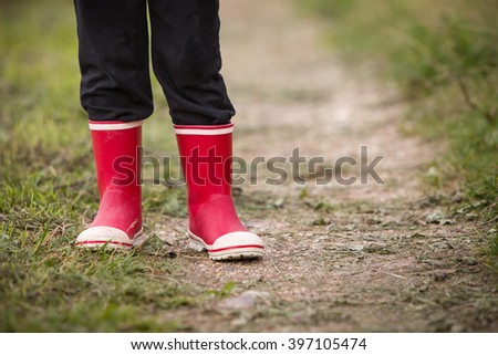 little kid boy in rain rubber boots. leg's shot. Child in bright red shoes. On a countryside road, outdoors.