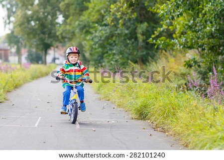 Little kid boy in red safety helmet and colorful raincoat riding his first bike on summer day. Active leisure for children outdoors. - stock photo