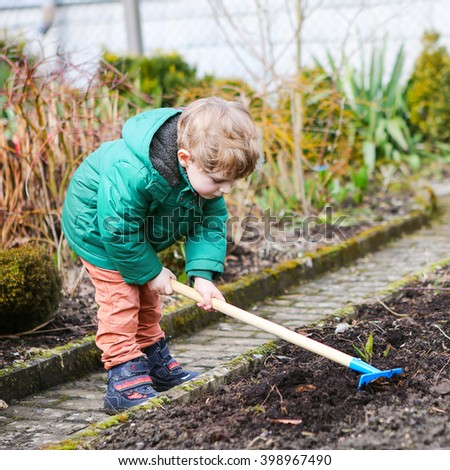 Little kid boy in spring with garden hoe, planting and gardening, outdoors. Funny toddler having fun with working in garden. - stock photo