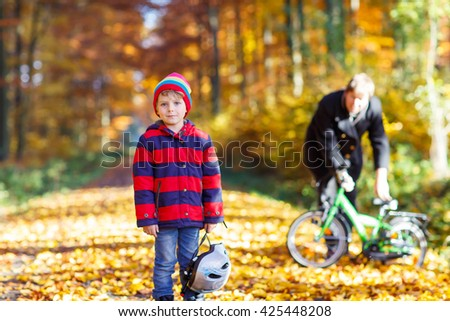 Little kid boy of five years and his father in autumn forest with a bicycle. Active child putting his bike helmet. Safety, sports, leisure with kids concept. - stock photo