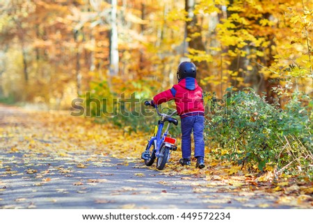 Little kid boy of four years in autumn forest with a bicycle. Active child wearing bike helmet. Safety, sports, leisure with kids concept. - stock photo