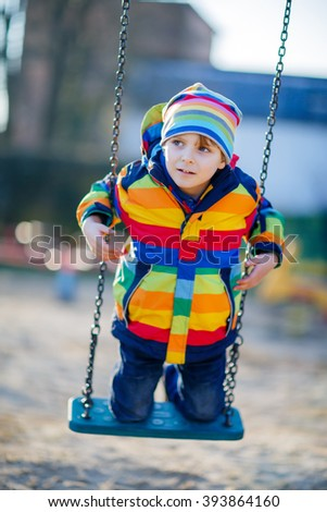 Little kid boy of 5 having fun with chain swing on outdoor playground. child swinging on warm sunny spring or autumn day. Active leisure with kids. Boy wearing colorful clothes - stock photo