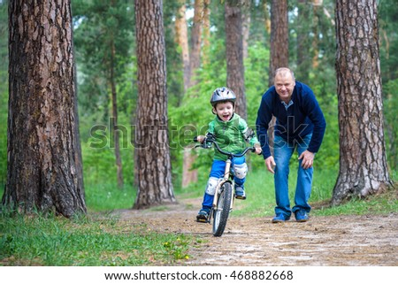 Little kid boy of 3 years and his father in autumn forest with a bicycle. Dad teaching his son. Man happy about success. Child with helmet. Safety, sports, leisure with kids concept.