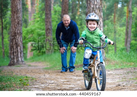Little kid boy of 4 years and his grand father in summer forest with a bicycle. Grandpa teaching his boy. Man happy about success. Child with helmet. Safety, sports, leisure with kids concept.