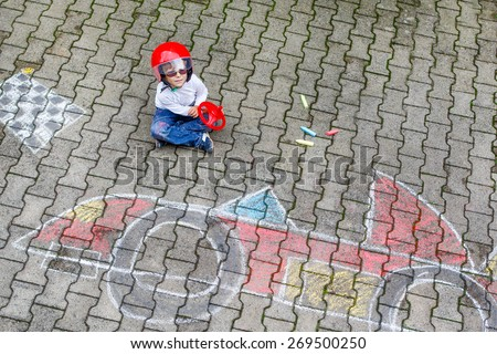Little kid boy painting race car picture with colorful chalks. Creative leisure for children outdoors in summer - stock photo