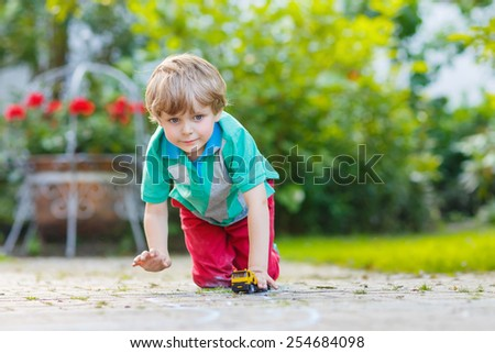 Little kid boy playing with car toy in summer garden. Active outdoors leisure for children on hot summer sunny day. Family lifestyle - stock photo