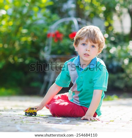 Little kid boy playing with car toy in summer garden. Active outdoors leisure for children on hot summer sunny day. Family lifestyle