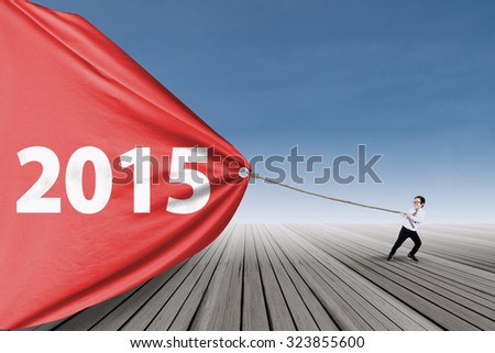 Little kid draw number 2015 on a big banner, shot outdoors - stock photo