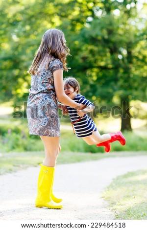 Little kid girl and her mom in rubber boots having fun together, family look, in summer park on sunny warm day. Long legs of woman. - stock photo