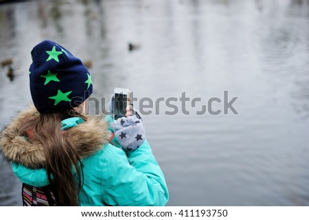 Little kid  girl in colorful autumn clothes making photo or video  of ducks  in the lake with smartphone in the city parkon beauty day - stock photo