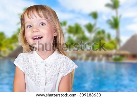 Little kid (girl) near the pool in tropical resort