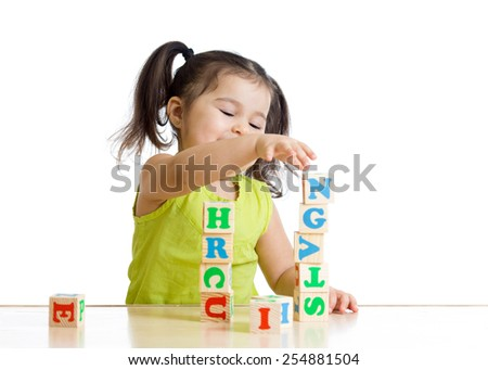 Little kid girl playing with wooden blocks with letters - stock photo