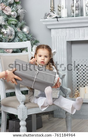 Little kid girl sitting in chair with christmas gift box