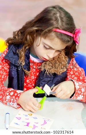 little kid girl working at school doing art work workshop  cutting with scissors - stock photo
