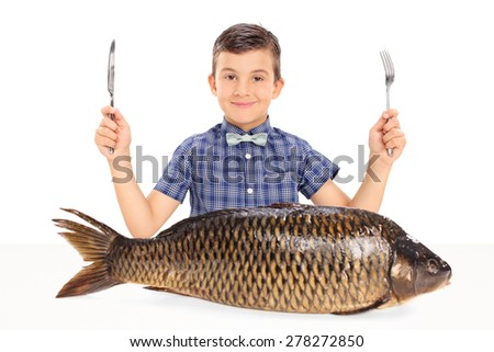 Little kid holding a fork and a knife seated at a table with a huge raw fish in front of him isolated on white background - stock photo