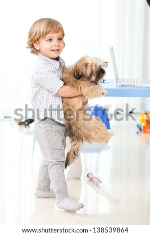little kid holding his pet at home, two years old child playing with his dog in the living room - stock photo