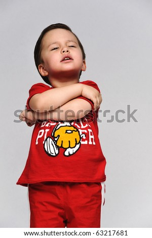 Little kid in a red sports outfit hands folded on his chest looking moody