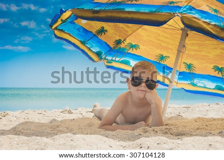 Little kid in a sunglasses lying on a sandy beach under colorful umbrella - stock photo