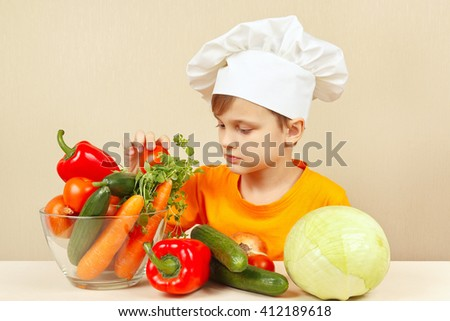 Little kid in chefs hat chooses vegetables for salad at the table - stock photo