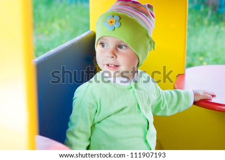 Little kid in the playing lodge in the playground.