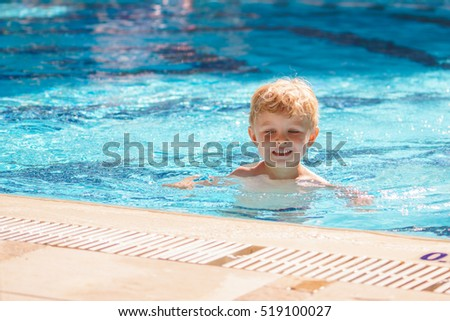 Little kid is learning to swim alone in the resort pool. Focused face. Sunny day. Blue water.