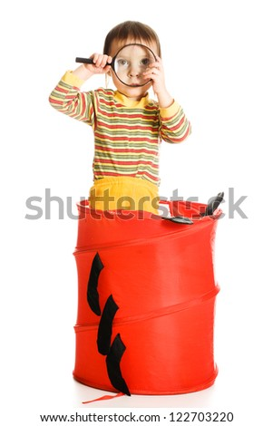 Little kid looking out of basket with a magnifying glass on a white background. - stock photo