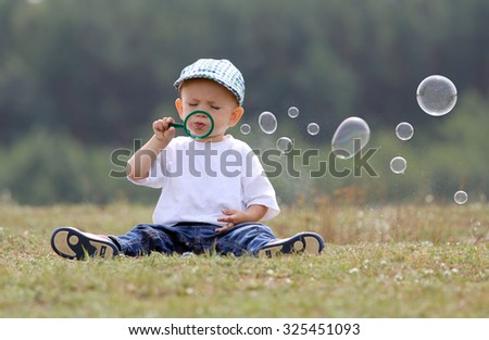 Little kid making soap bubbles in the park