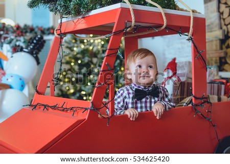 little kid near christmas tree playing and smiling