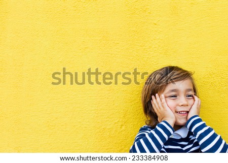 little kid on a yellow wall, wearing a stripes navy sweater - stock photo