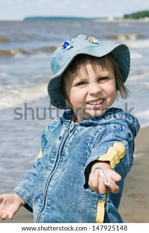 Little kid on the autumn beach. - stock photo