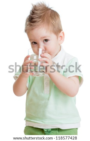 Little kid or child drinking water from glass isolated on white. It is a boy. Studio shot. - stock photo