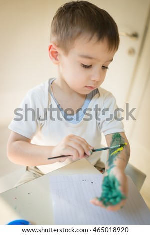 Little kid painting and drawing on board canvas at home
