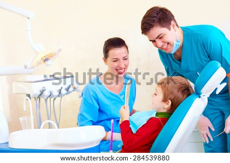 little kid, patient checking the result of medical procedure in dental clinic - stock photo