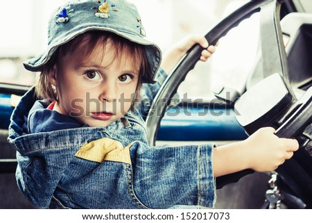 Little kid playing at the wheel of car