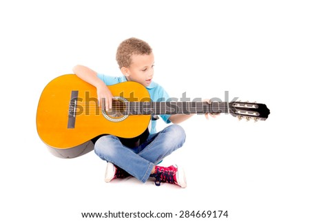 little kid playing guitar isolated in white - stock photo