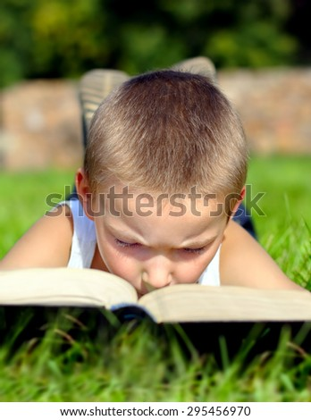 Little Kid read the Book on the Summer Meadow - stock photo