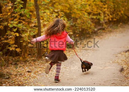 Little kid running and walking with a dachshund puppy. Love to animals concept - stock photo