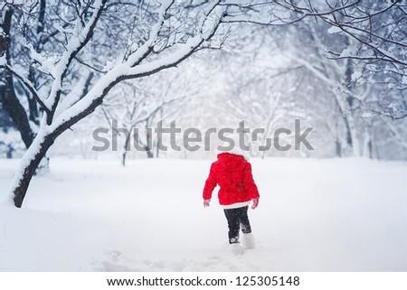 Little kid  running on snow - stock photo