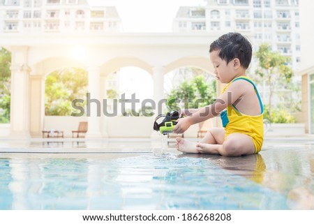 Little kid sitting at the poolside - stock photo