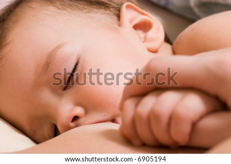 Little kid sleeping and breast-feed