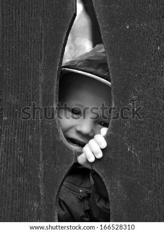 Little kid smile behind wooden fence - stock photo