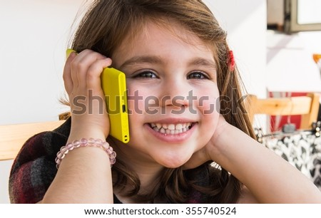 Little kid talking to mobile - stock photo