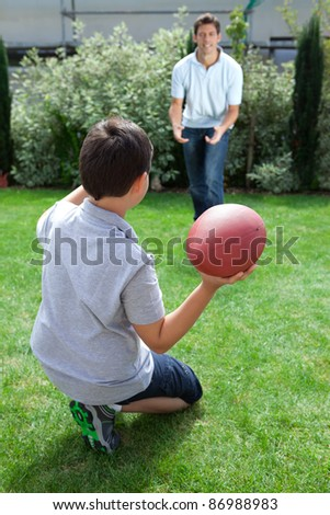 Little kid throwing football to his father in backyard