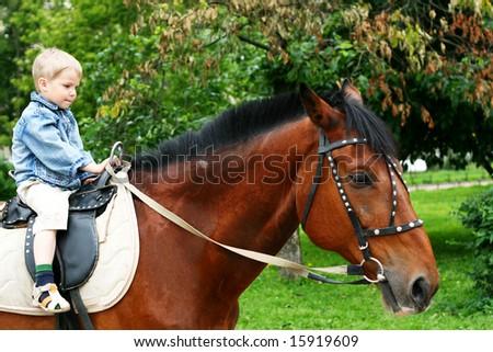 Little kid to go on horseback - stock photo