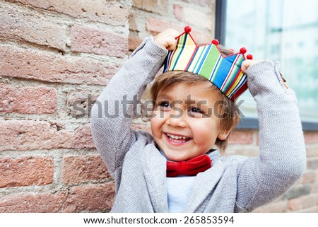 little kid with a crown on a brick wall - stock photo