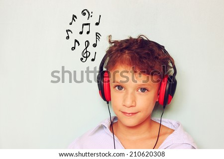 little kid with headphones  listening to music and notes sketches  - stock photo