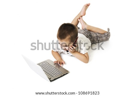 little kid with laptop talking on mobile phone