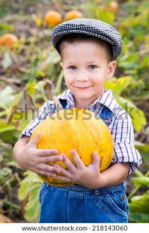 Little kid with pumpkin in hands on vegetable garden - stock photo